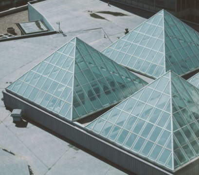 Glass pyramid structures built into the top of a commercial building.