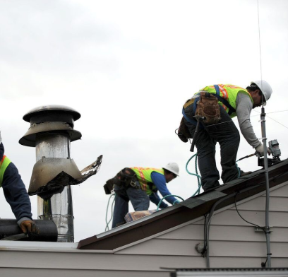Three contractors with protective gear work on top of a roof.